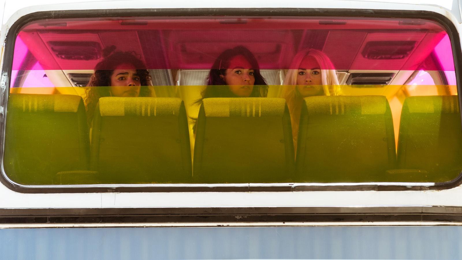 de gauche à droite, gina, coral et wendy au fond d'un bus pendant leur épopée
